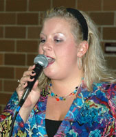 Laura holds the microphone while singing.